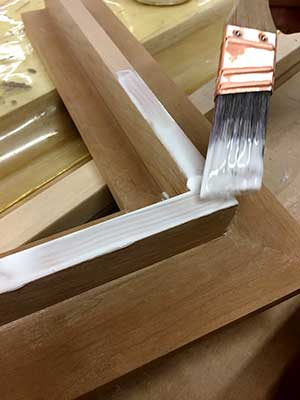 brushing-glue-cherry-hardwood-gilded-frame-prep
